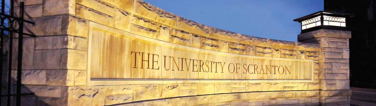 Stone sign for the University of Scranton at twilight.